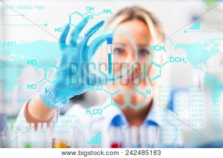 Young Attractive Female Scientist In Protective Eyeglasses And Gloves Examining Test Tube With Red L