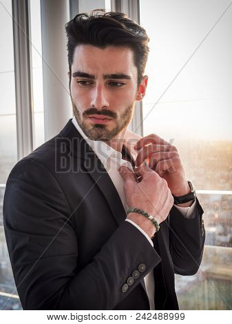 Handsome Serious Businessman Standing Inside Modern Building Next To Big Window, Looking Out