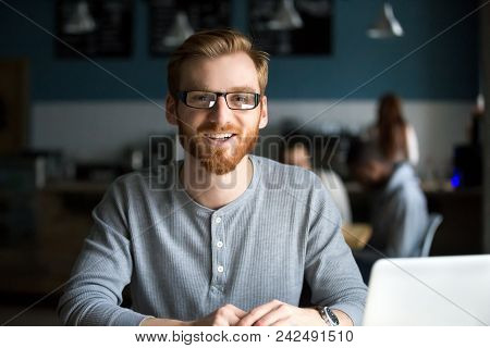 Smiling Redhead Man With Laptop Looking At Camera In Cafe, Happy Millennial Guy In Glasses Posing In