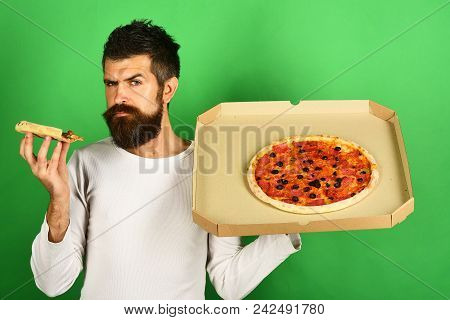Pizza. Handsome Sexy Bearded Man With Serious Face Eating Pizza. Man Eating Pizza And Holds Box. Hip