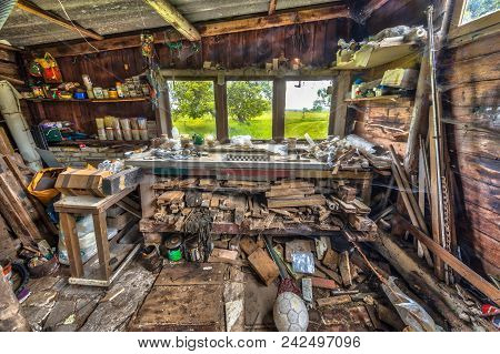 Extremely messy workbench in a wooden barn poster