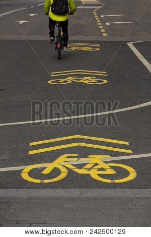 Yellow Sign Of A Bicycle Path Drawn On The Asphalt Road. Lanes For Cyclists. Cyclist On Urban Cyclew