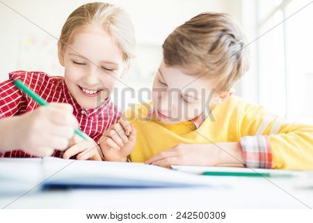 Two cute youngsters with crayons looking at their funny drawing in copybook