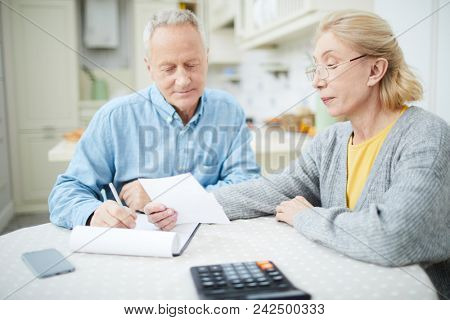 Senior couple sitting by table in the kitchen and planning family budget for various expenses