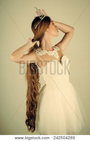 Haircare and prom queen. Hairdresser and cosmetics. Beauty salon and wedding fashion. Woman with long hair white dress and crown. Girl has fashionable makeup and healthy hair on grey background. poster