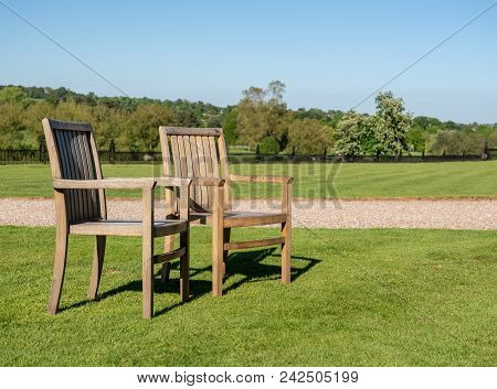 Teak Chairs In A Large Expansive Garden With Trees In Background