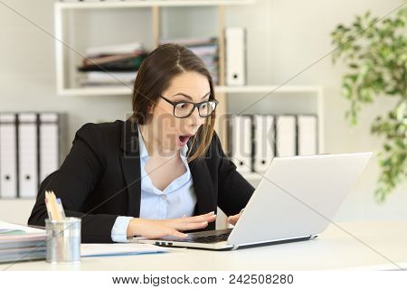 Amazed Office Worker Reading Good News In A Computer On A Desktop