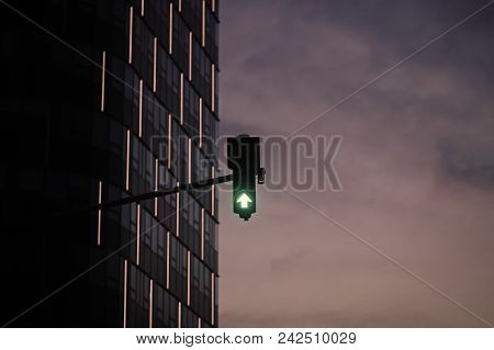 Green Traffic Light In City On Cloudy Grey Sky Background. Architecture, Structure, Design. Signal,