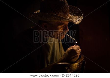 Horizontal Low Key Head Shot Of A Caucasian Rugged Looking Man Lighting A Cigarette With The Flame L