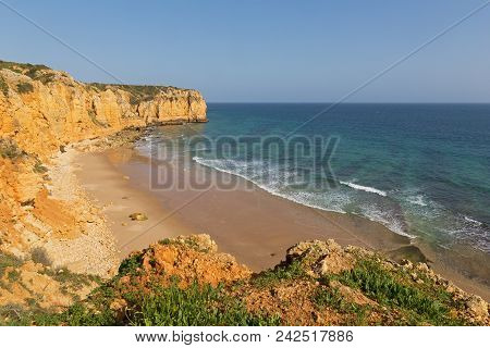 Atlantic Ocean Sandy Beach Formed Between Two Cliffs At Sunset, Algarve, Portugal. Waves Are Rolling