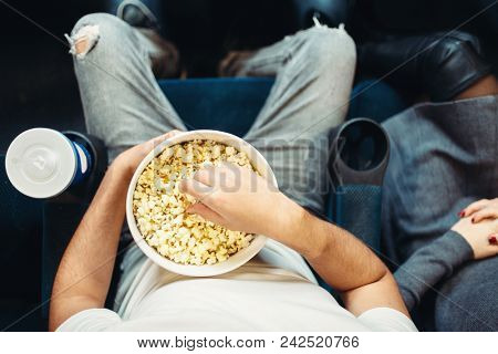 Male person with popcorn in cinema, top view