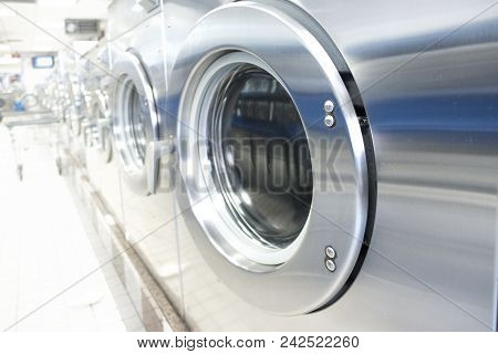 Laundromat With Line Of Commercial Washing Silver Appliances