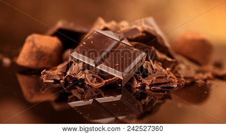 Assorted Chocolate Candies. Chocolate Sweets. Candy Design over dark brown Background. Various Chocolates. Confectionery