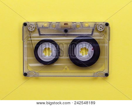 Transparent Compact Audio Tape Cassette On Yellow Background - Closeup