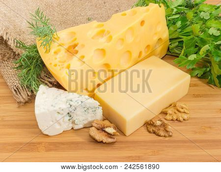 Pieces Of Medium-hard Swiss Cheese, Hard Cheese, Blue Cheese With Greens And Walnut Kernels On The B