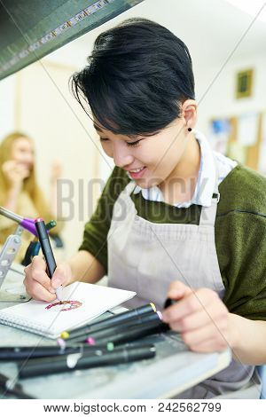Portrait Of Smiling Young Asian Woman Drawing Sketches In Glassworking Studio, And Enjoying Work Rea