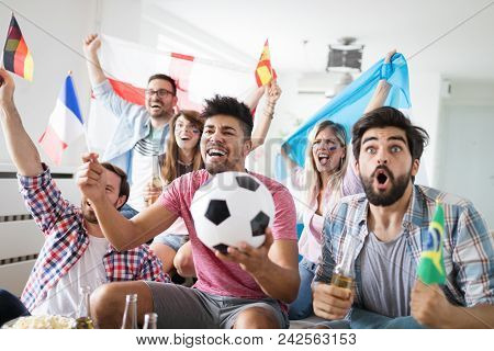 Cheerful And Happy Group Of Friends Watching Football Game On Tv.