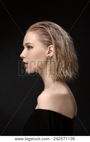 Beautiful Girl Model Blonde With Wet Hair On A Black Background In Profile. Hair Up To The Shoulders