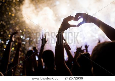 Portrait Of Happy Dancing Crowd Enjoying At Music Festival
