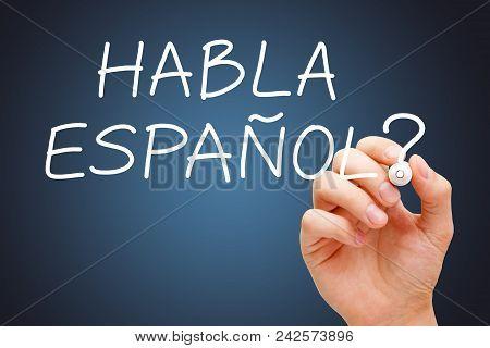 Hand Writing Question Habla Espanol - Speak Spanish With White Marker On Dark Blue Background.