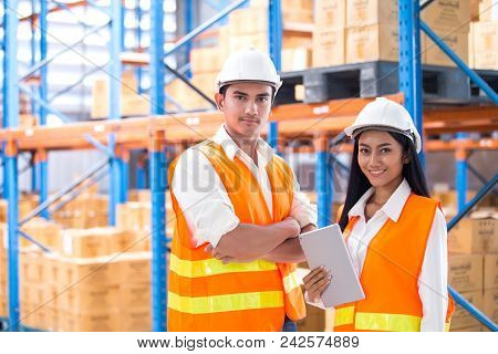 Male And Female Industrial Engineers Looking To Camera With Attractive Smiling. They Work In Industr