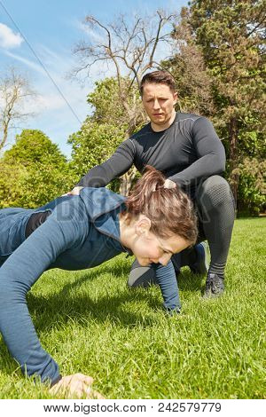 Woman making push ups with Personal Trainer at the park
