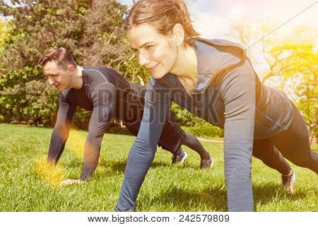 Couple making fitness training push ups at the park
