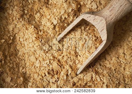 Nutritional Brewers Yeast Flakes With Wooden Scoop. Top View With Copy Space