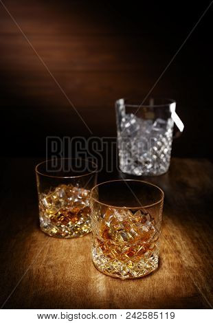A Spotlight On A Two Crystal Glass Of Scotch Whisky With A Ice Bucket In The Backghround, Shot On A