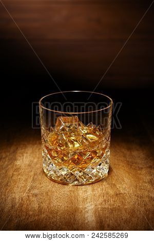 A Spotlight On A Single Crystal Glass Of Scotch Whisky, Shot On A Wooden Table Top.