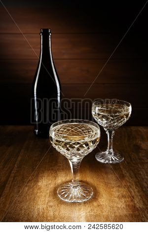 Spotlight On Two Champagne Crystal Glasses With A Bottle In Background, Shot On A Antique Wooden Tab