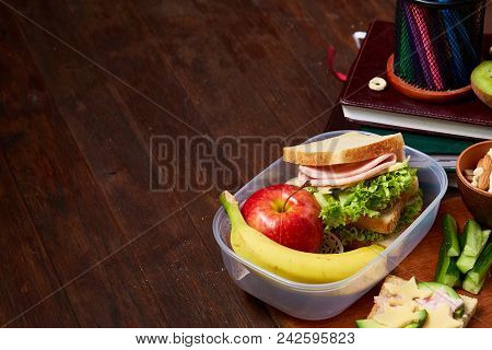 Concept Of School Lunch Break With Healthy Lunch Box Full Of Sandwiches, Banana, Apples And School S