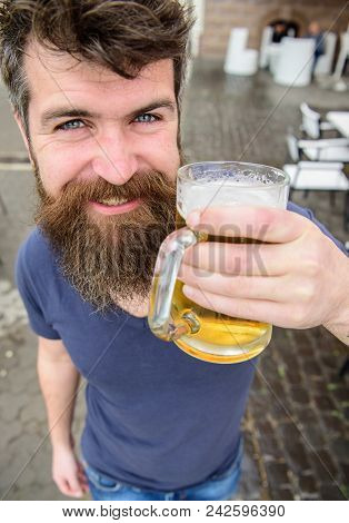 Guy having rest with cold draught beer. Hipster on smiling face drinking beer outdoor. Draught beer concept. Man with beard and mustache holds glass with beer while relaxing at cafe terrace. poster