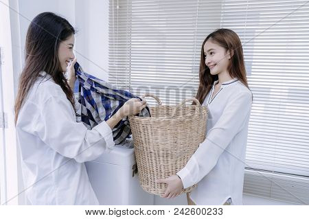 Same sex couple women asian doing housework or chores helping with washing machine laundry loading clothes and in the room, Lesbian relationship female living together. poster