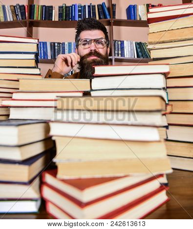 Teacher Or Student With Beard Wears Eyeglasses, Sits At Table With Books, Defocused. Scientific Rese