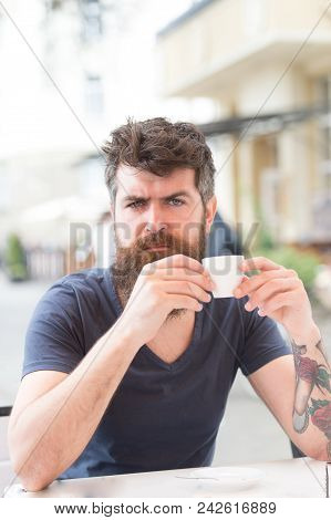 Coffee Break Concept. Man With Long Beard Looks Serious. Man With Beard And Mustache On Strict Or Se