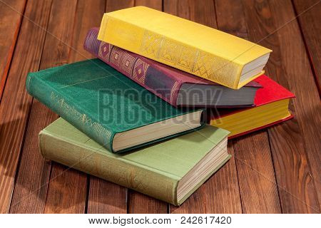 Hardback Book In A Firm Cover Lie One On One On A Surface Of A Wooden Table.
