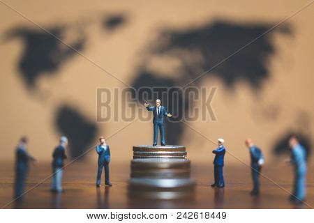 Miniature People: Businessman On Stack Of Coin, Money And Financial Business Success Concept.