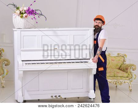 Courier delivers furniture, move out, relocation. Loader moves piano instrument. Man with beard worker in helmet and overalls lifts up, efforts to move piano, white background. Heavy loads concept. poster