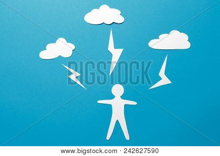 The Concept Of Man Is Under Threat. A Paper Man Origami Stands Under Lightning From The Clouds On A