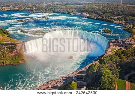 Aerial Top Landscape View Of Niagara Falls And Tour Boat In Water Between Us And Canada.  Horseshoe
