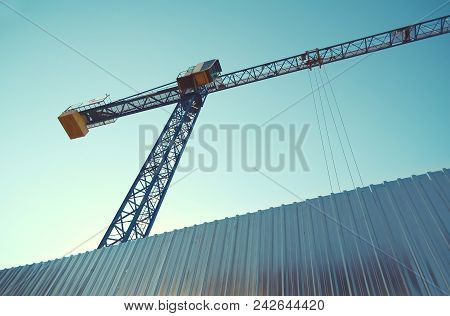 Building Crane Behind Tin Fence On Wone The Cloudless Sky, The View From The Bottom Up.