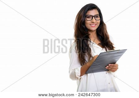 Studio Shot Of Young Happy Persian Woman Smiling While Holding Clipboard With Eyeglasses Isolated Ag