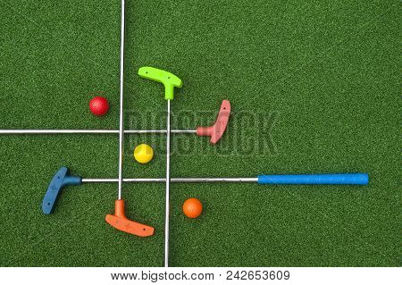 Criss Cross Of Colorful Mini Golf Clubs And Balls On Artificial Grass