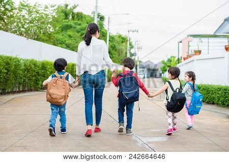 Group Of Preschool Student And Teacher Holding Hands And Walking To Home. Mom Bring Her Children Go