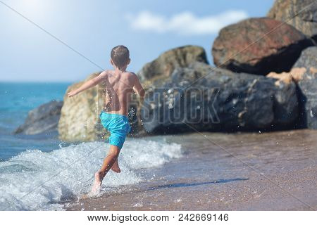 Caucasian Boy Is Running In The Water Along The Sea Shore. Back View.