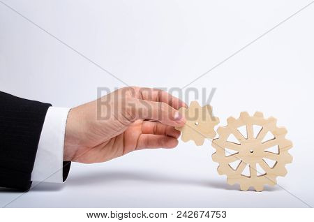 Hand Of Businessman In Suit Holds The Gear To Another Gear Wheel. The Hand Connects Two Round Gears.