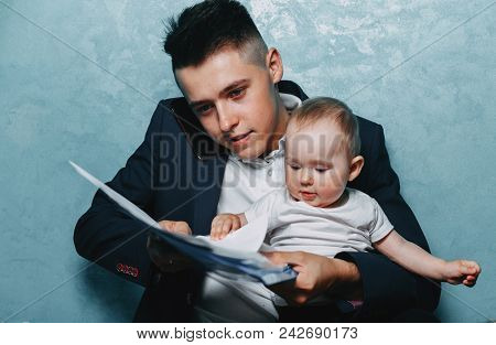 Father Working At Home Office And Holding Daughter On His Lap. Businessman Looking After Baby Girl A