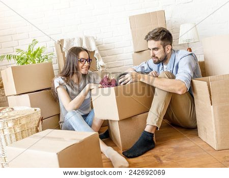 Casual Woman And Man With Stack Of Boxes Unpacking Things While Moving To New Place Of Living.