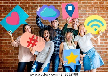Cheerful friends holding social media icons